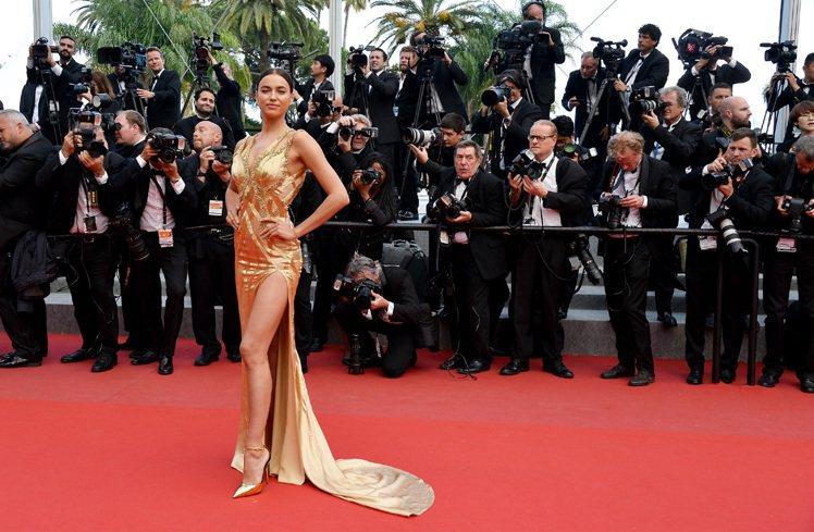 伊蓮娜身穿 Versace 金色禮服,金色綴飾與印花隨著曲線而下,加上鏤空肩帶與...