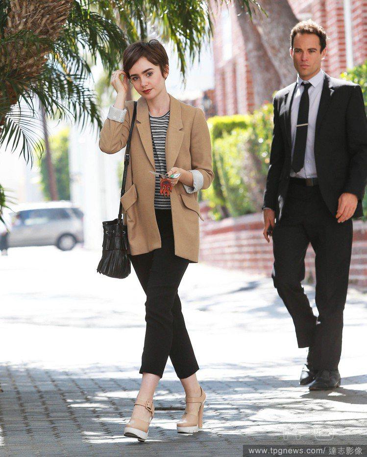 莉莉柯林斯將平凡無奇的條紋上衣與黑色七分褲,搭配駝色外套,就立刻亮眼起來,也帶來...