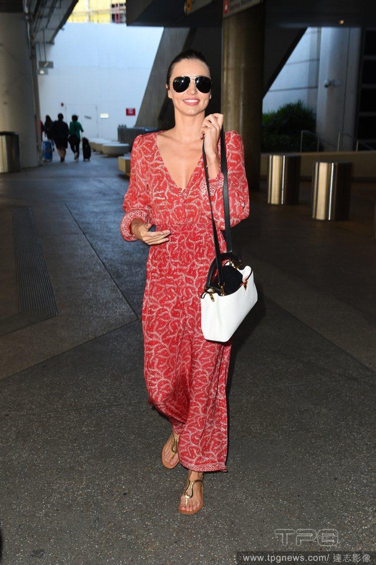 米蘭達柯爾的紅色 V 領連身褲,寬鬆褲擺帶來裙子般的飄逸效果,搭配金色涼鞋展現民...