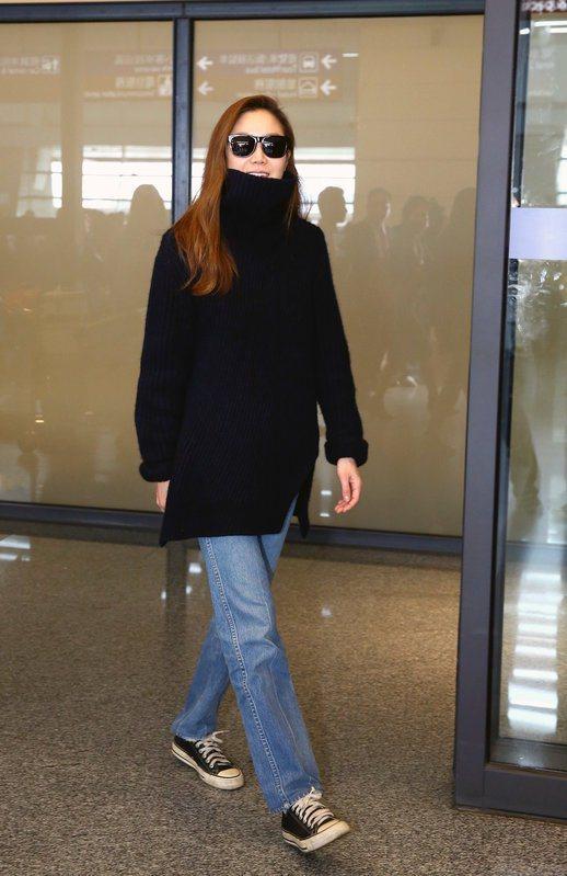 孔曉振以一件寬鬆長版高領毛衣,搭配寬版牛仔褲與帆布鞋率性亮相,展現摩登率性的機場...