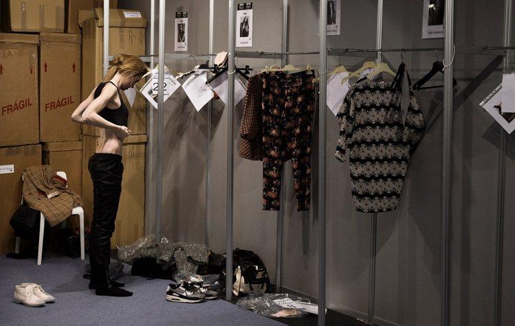 模特兒在伸展台上光鮮亮麗,但到了後台,大方更衣、喬奶,又是不同模樣。圖/美聯社
