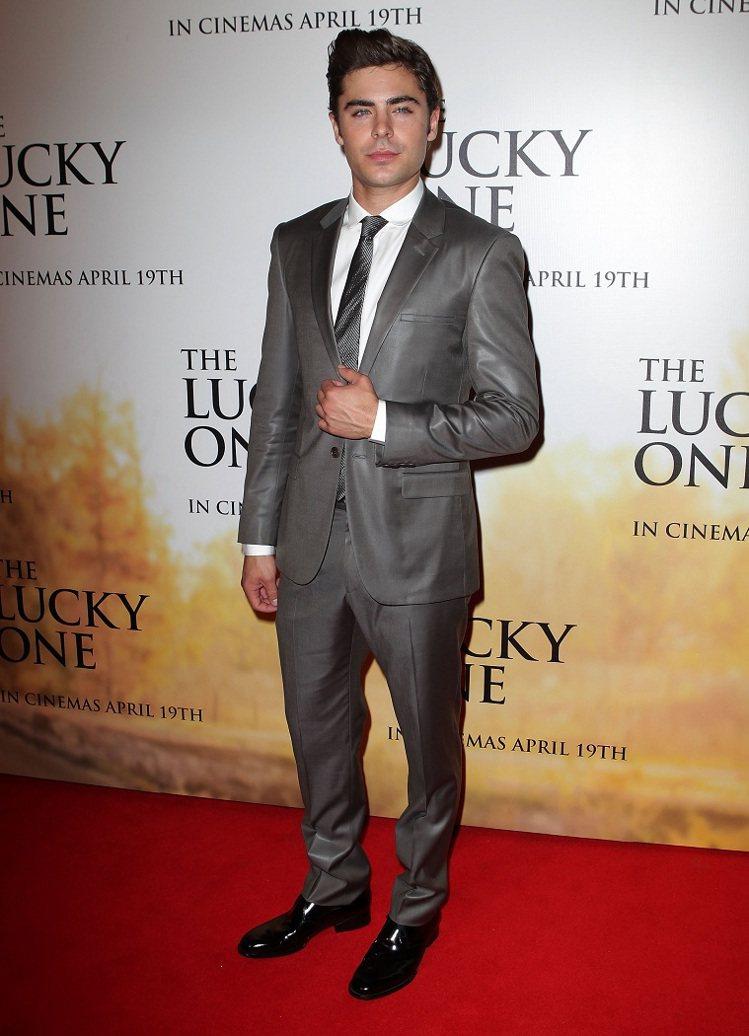 柴克則以灰褐色的Calvin Klein亮面翻領西裝搭白色襯衫展現紳士氣質。圖/...