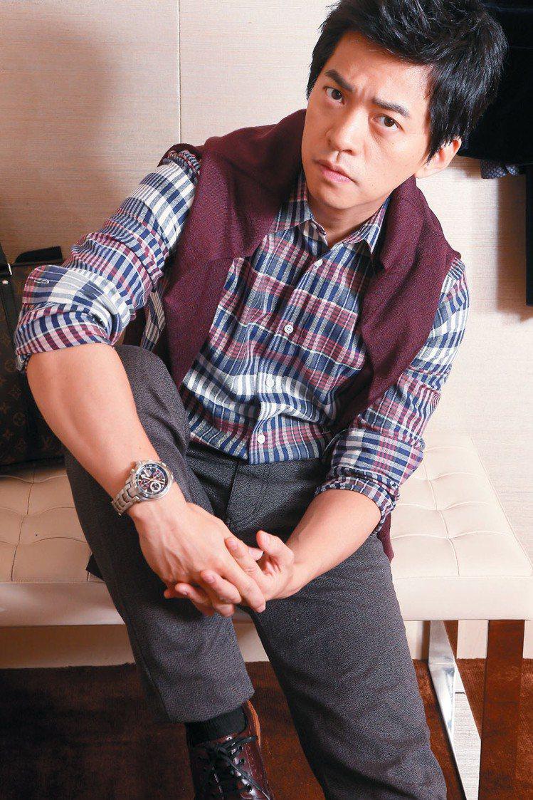 李健穿LV格紋襯衫23,900元、牛仔褲28,600元、酒紅色針織上衣25,50...