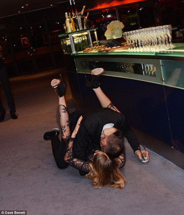 Cara Delevingne酒後失態,和男伴跌坐在地上。圖/擷自Dailyma...