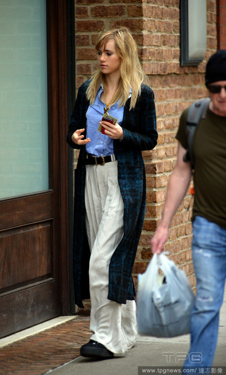 Suki Waterhouse 以淡藍色的襯衫搭白色寬管褲,還使用了皮帶拉高腰線...