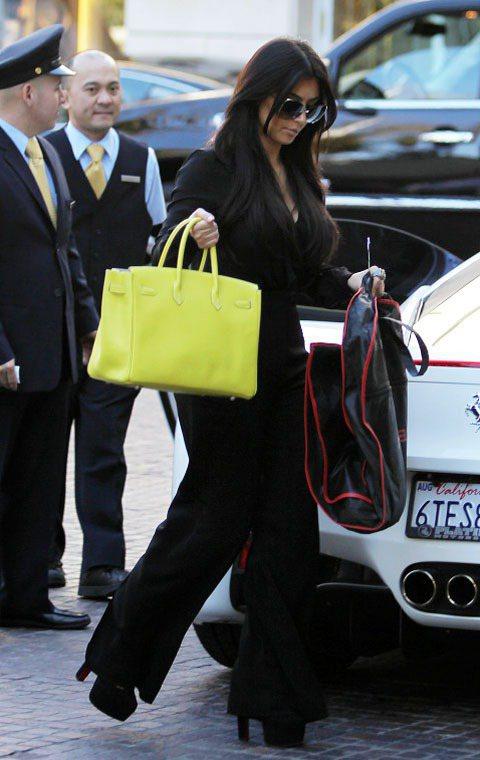 金卡達夏黃綠色柏金包與一身黑衣搭起來非常搶眼。圖/達志影像