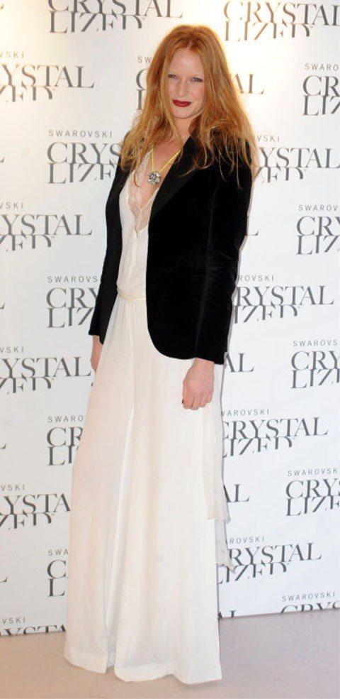 超模Olivia Inge的白色雪紡薄透寬版連身褲如禮服般優雅,搭黑色西裝外套很...