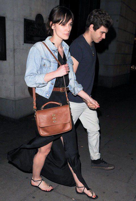 綺拉奈特莉一身黑色開叉長洋裝搭淺色丹寧夾克,以咖啡色仿舊腰帶、包包帶出西部率性復...