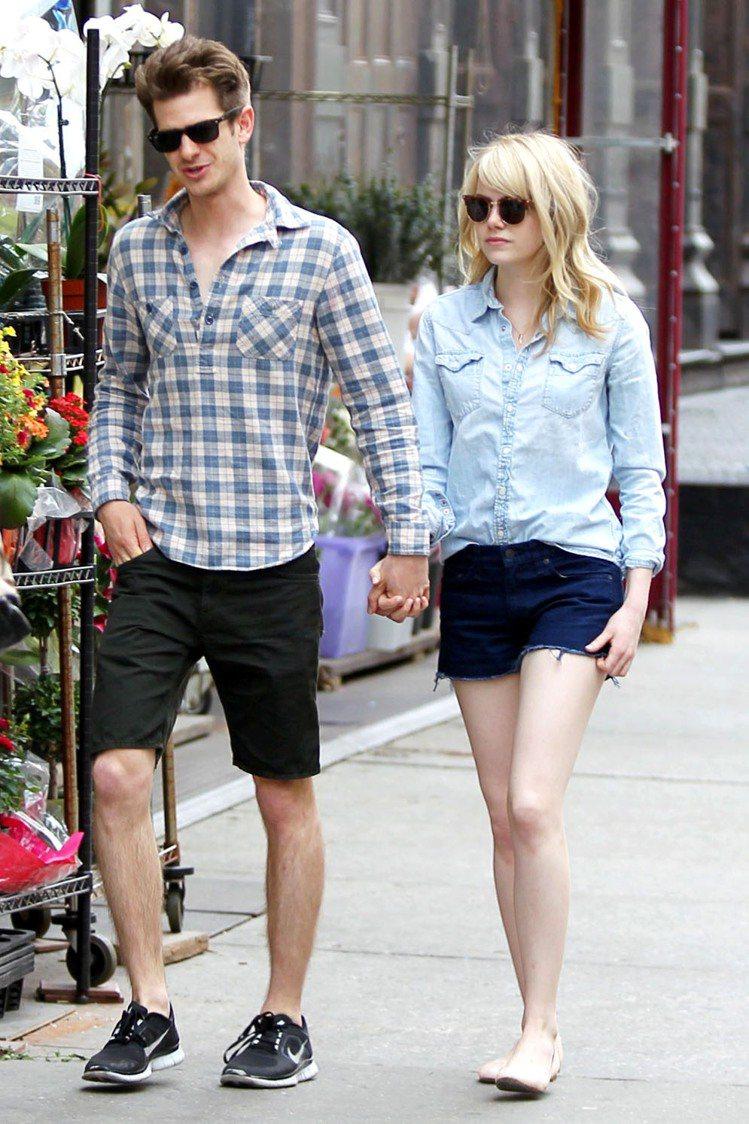 艾瑪史東以輕薄淺色牛仔襯衫搭深色牛仔褲露出美腿和男友一同上街,簡單的穿搭用不同色...