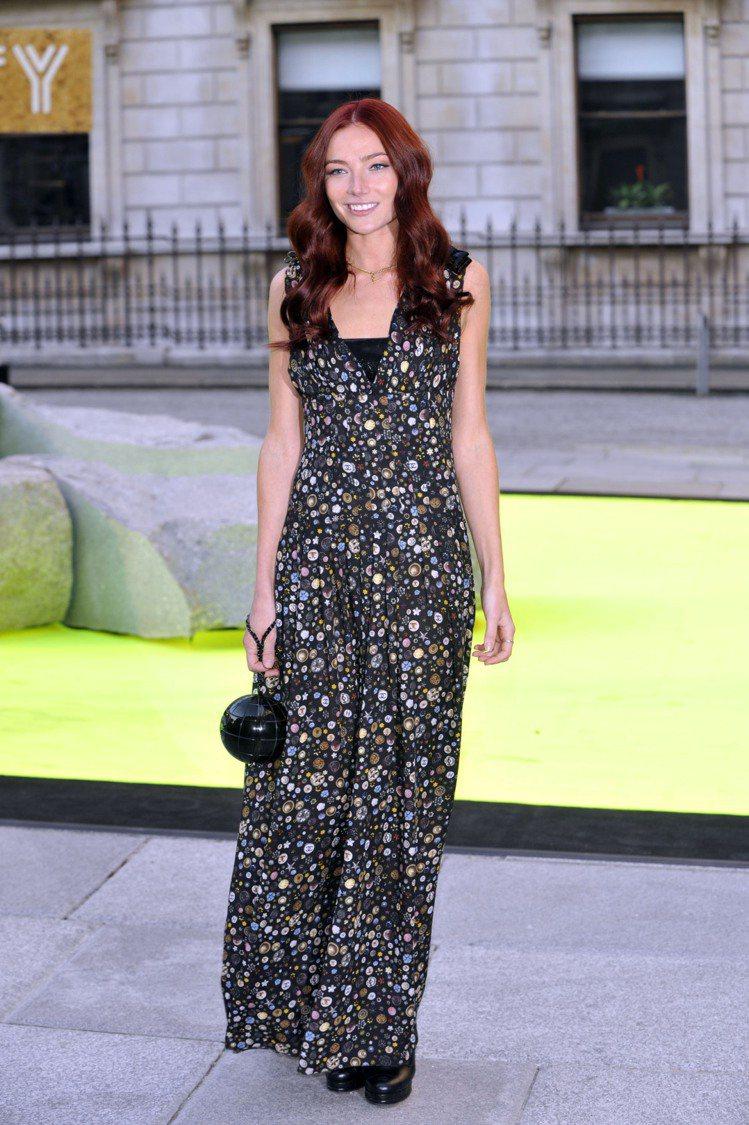 英國It Girl Clara Paget 以一身印花長洋裝搭配小巧的球狀手拿包...