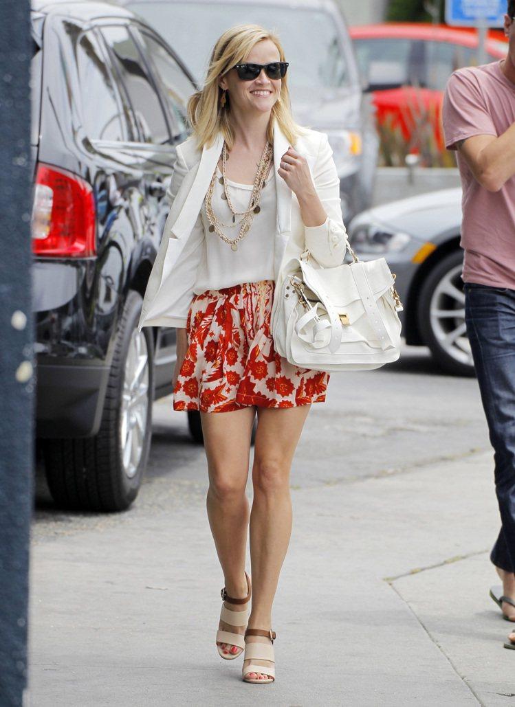 瑞絲薇斯朋白色西裝外套搭白T恤,配橘色印花裙露出美腿,看來瘦身效果不錯。裸色系跟...