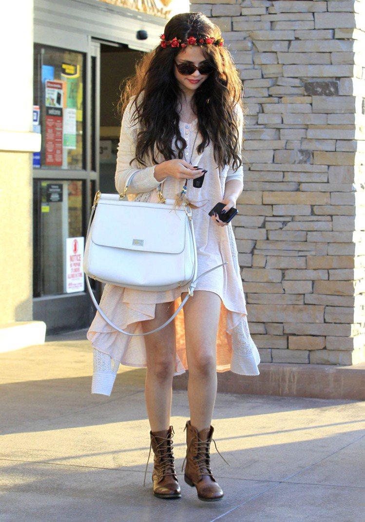 席琳娜戴花圈在頭上搭配前短後長的洋裝配靴子,來個嬉皮搖滾女孩風。圖/達志影像