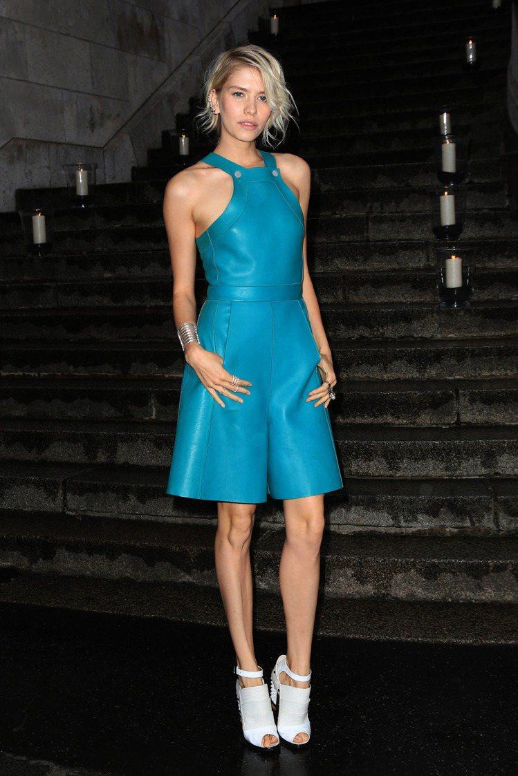 寶藍色皮革連身褲裙搭白色露指粗跟鞋。圖/達志影像