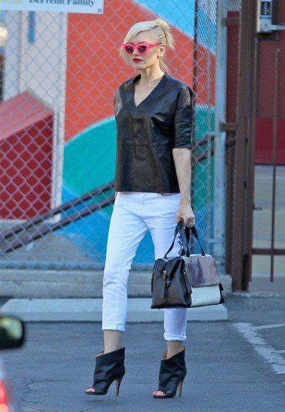 關史蒂芬妮的黑色仿皮革薄上衣搭白色八分褲,套上黑色露指踝靴帥氣有型,再搭同樣配色...