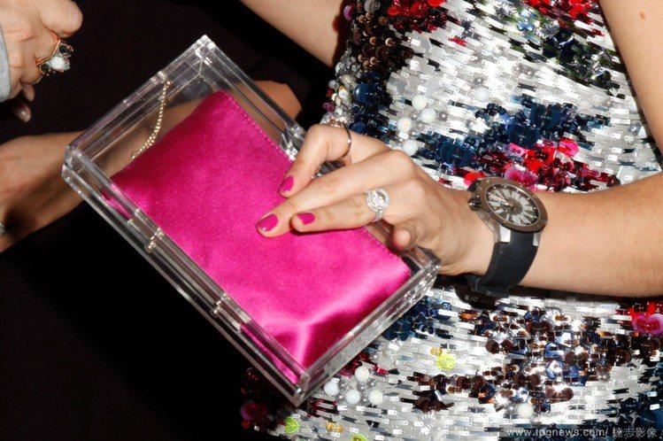 桃紅漆皮手拿包搭配閃亮服裝,將包包放在透明盒內的巧思,展現出精緻高雅的格調。圖/...