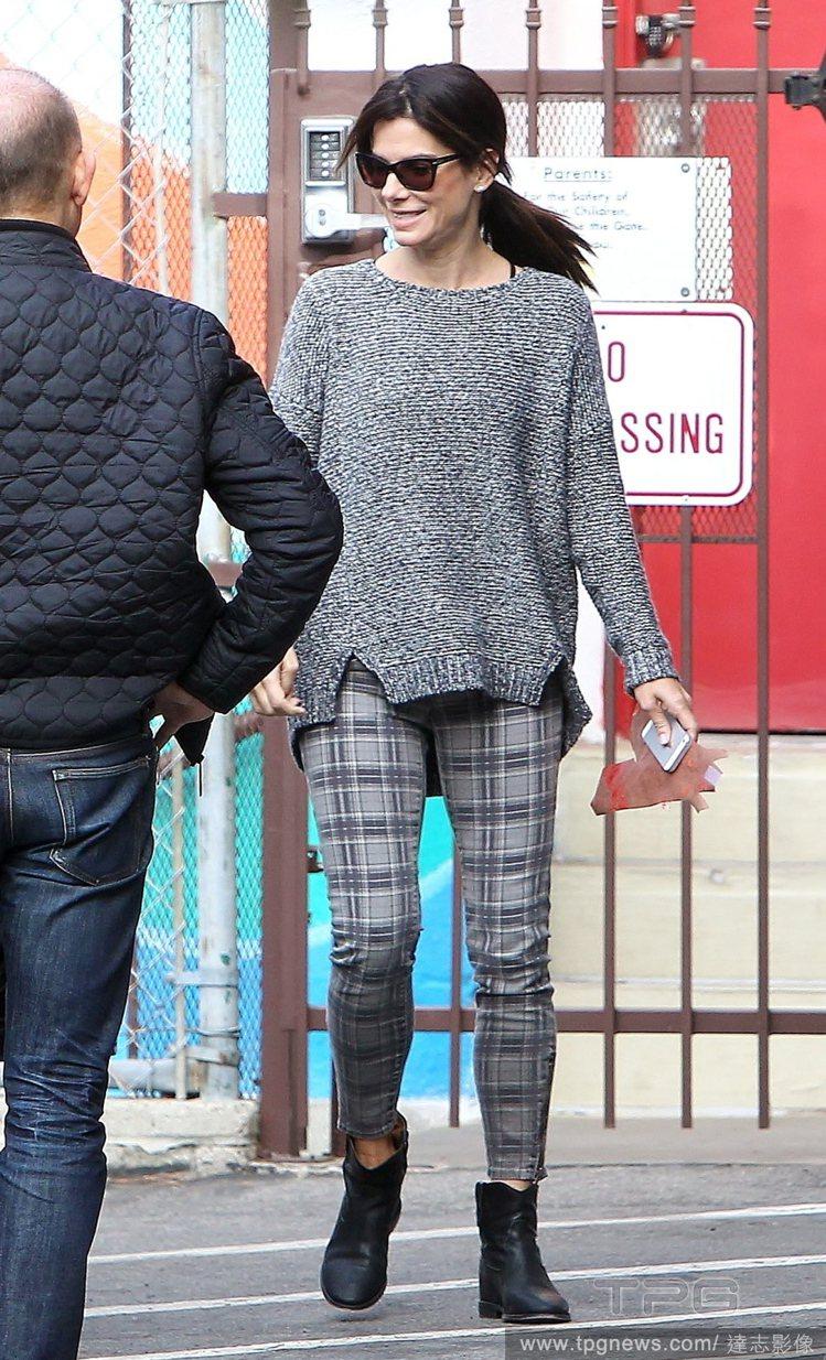 珊卓布拉克的灰色系穿搭看來舒適自在,上衣衣擺的剪裁非常有設計感,格紋褲比起綿褲又...