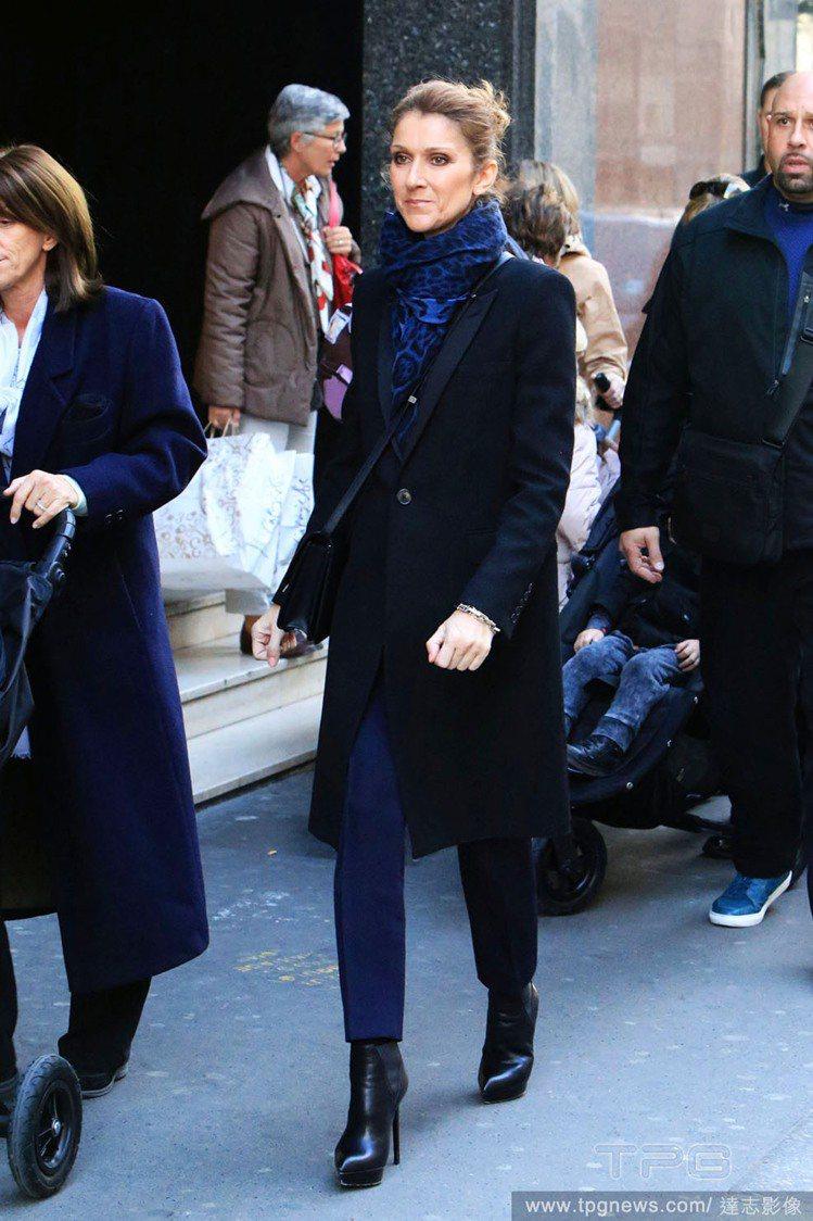 席琳狄翁一身黑色長大衣內搭深藍色褲款,她選擇了深藍豹紋圍巾來完成整體配色,不過度...