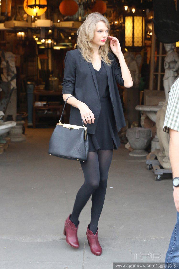穿了一身黑還提黑包包的泰勒絲(Taylor Swift),以鮮豔紅唇與暗紅色踝靴...