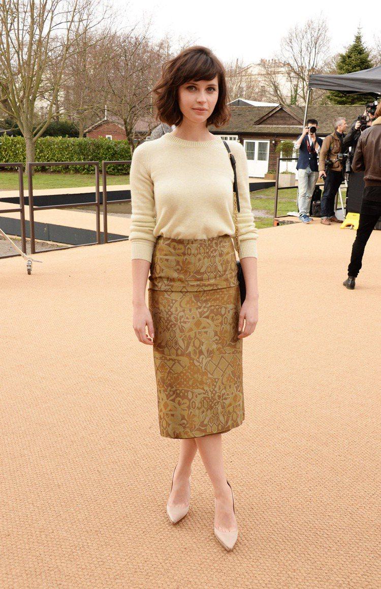英國女星 Felicity Jones 穿米色毛衣搭配大地色印花裙,看起來十分清...