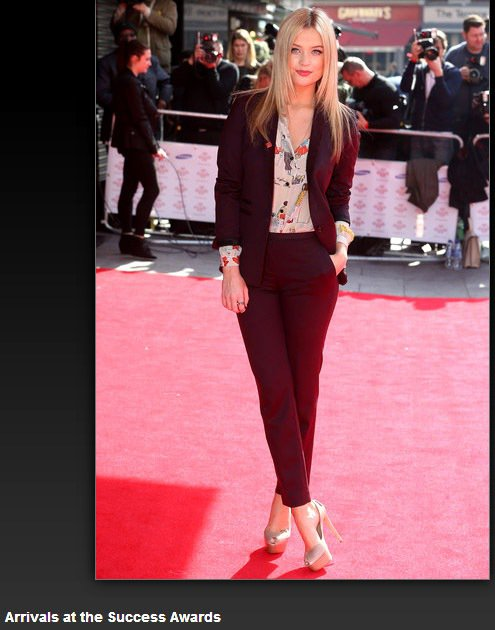MTV 主持人 Laura Whitmore 穿著酒紅色西裝褲套裝,內裡的大地色...