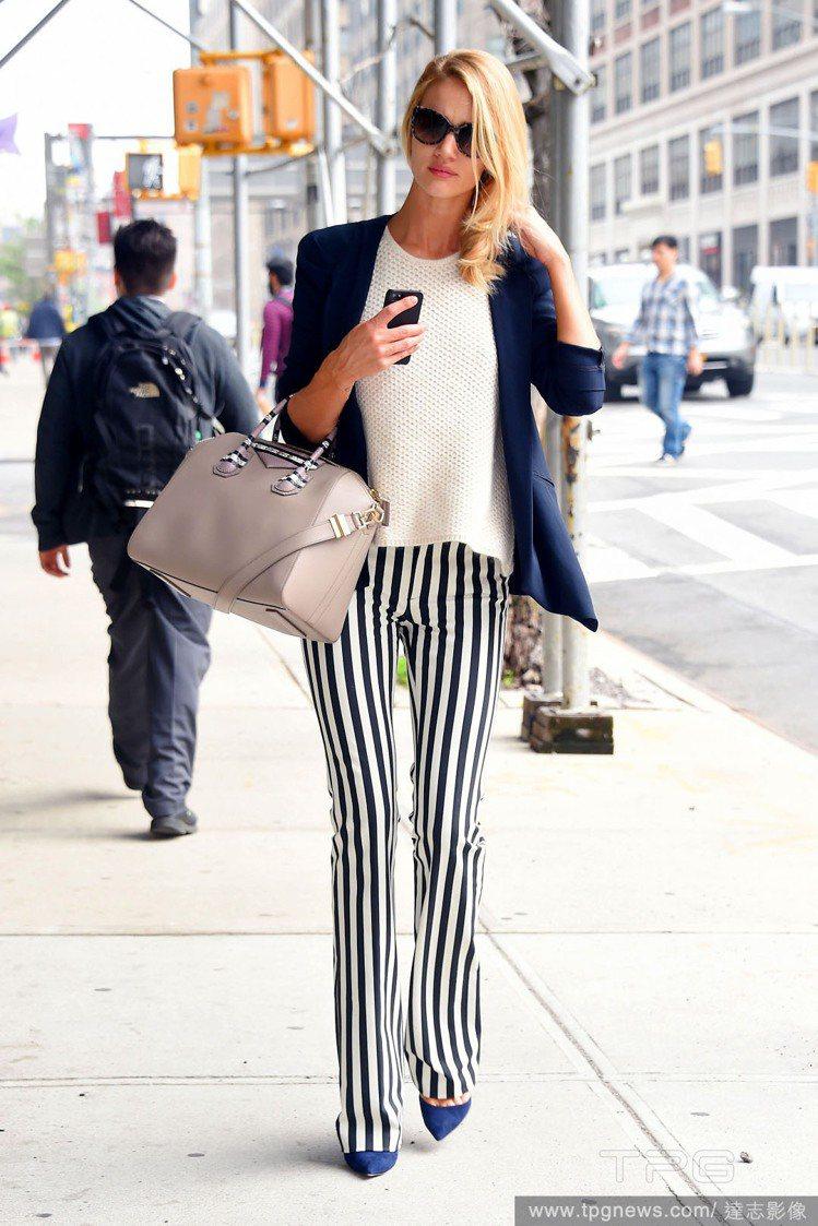 蘿西杭亭頓選穿直條紋的寬版喇叭褲搭配深藍色西裝,一身俐落風格瀟灑摩登。拎著最愛的...
