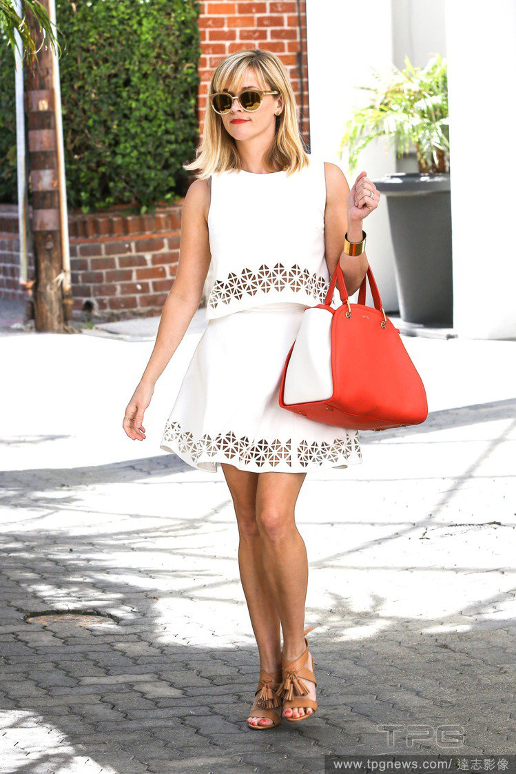 瑞絲薇斯朋身穿白色套裝式洋裝,並以淺咖啡雙色墨鏡、金屬手環與駝色流蘇涼鞋點綴洋裝...