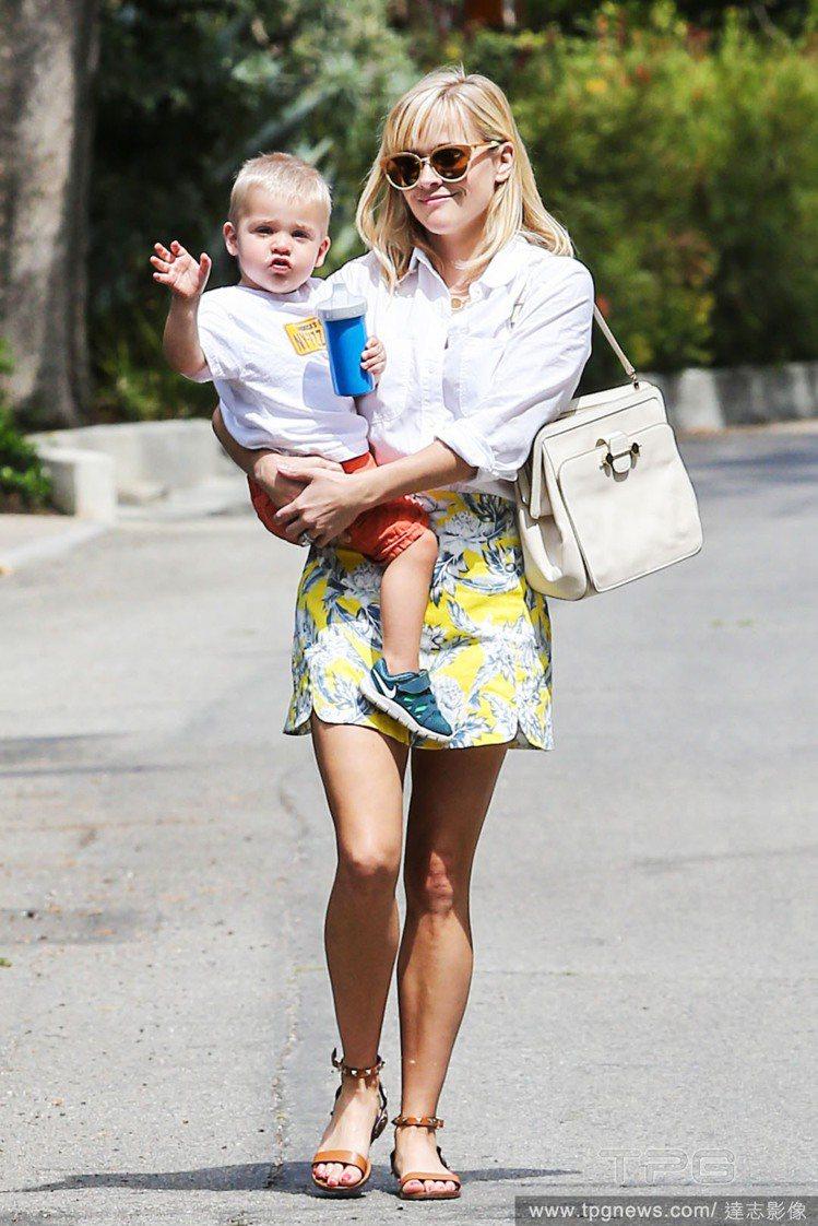 瑞絲薇斯朋以白襯衫搭配黃色印花裙,並以咖啡色鉚釘涼鞋穿出都會俐落感,又帶有渡假氣...