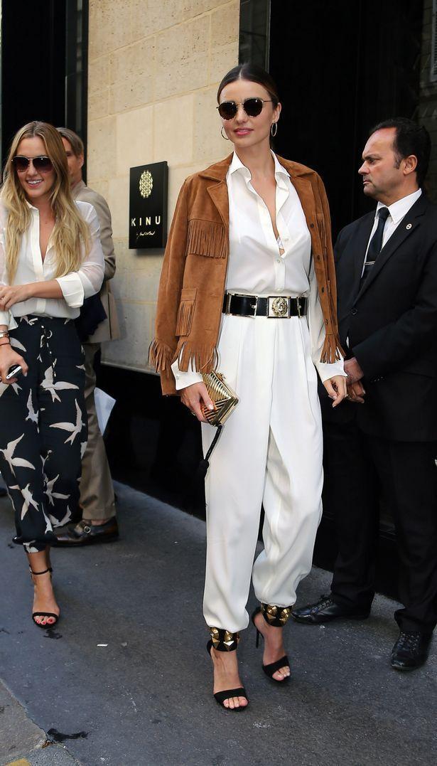 米蘭達柯爾以一身白色襯衫褲裝帥氣上街,深V線條超性感。金色腰帶、高跟鞋繫帶、手拿...