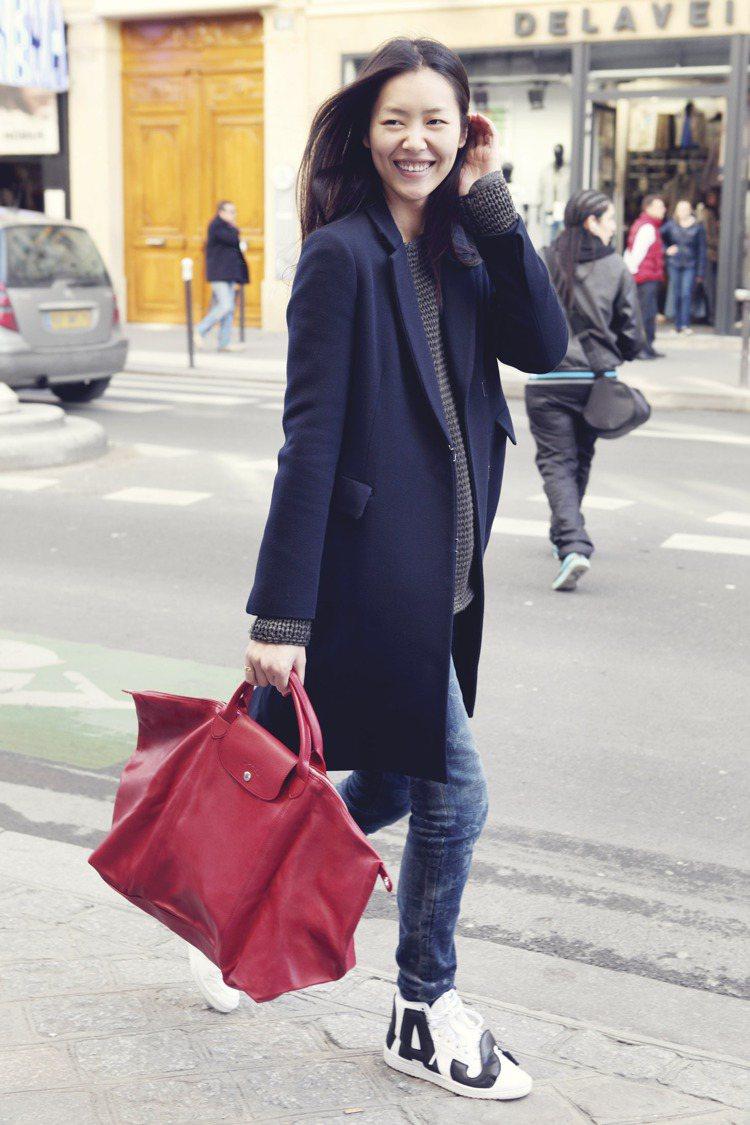 劉雯穿著深藍色大衣配休閒的條紋上衣與牛仔褲,腳上那雙白色球鞋頗具童趣調皮感,搭上...