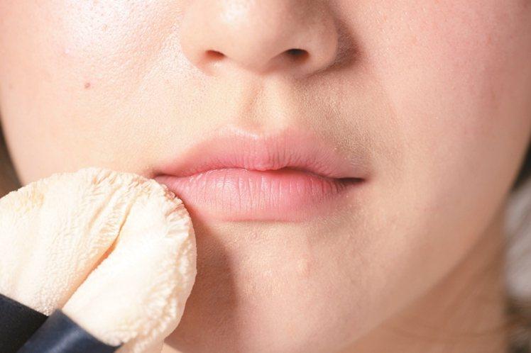 STEP1:用粉撲沾取蜜粉刷在唇上,就可以消去光澤創造霧面感。圖/美人誌提供
