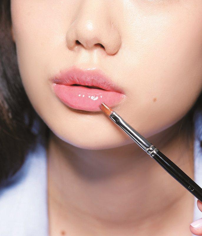 STEP1:先擦透明唇蜜打底,讓雙唇帶有水潤光,再疊橘色口紅,唇色會更透。圖/美...