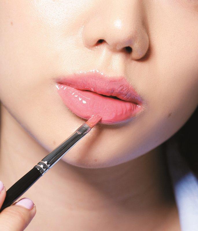 STEP2:上完唇膏後可在唇中疊上薄薄的一層橘色唇蜜,唇型的水潤度更明顯。圖/美...