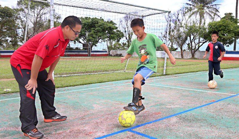 圖為台東寧埔國小的老師正在指導學生踢足球。報系資料照