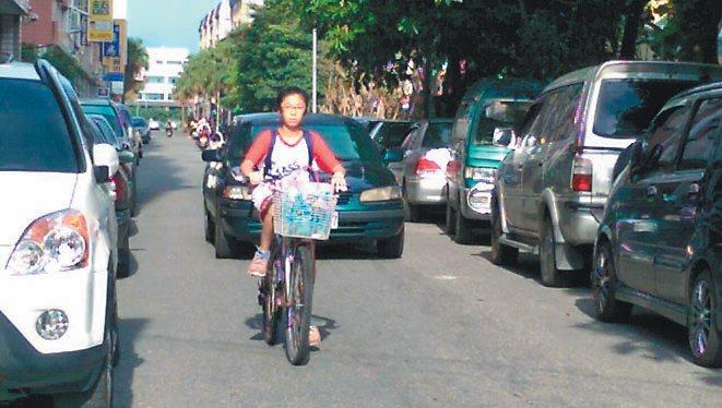 校舍一路兩旁停滿車,騎腳踏車的學生硬被 逼上車道。  記者戴永華/攝影