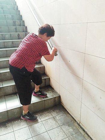 吳阿嬤(左)走曉陽人行地下道,因地面長青苔怕滑倒,緊扶扶手。 記者郭宣彣/攝影