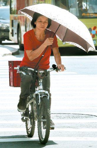 六月連續高溫破紀錄,炙陽讓騎車的婦人顧不得危險,一手撐傘一手騎車。 記者屠惠剛/...