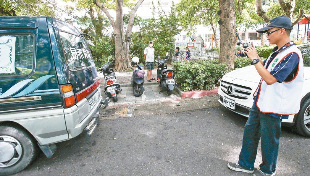 環保局相關人員巡視校園門口,看是否有車輛怠速超過三分鐘。 記者程宜華/攝影