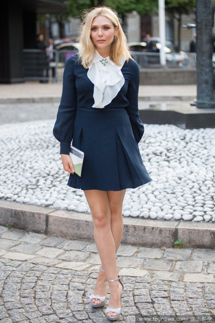 伊莉莎白奧森身穿黑白洋裝,襯衫領搭配波浪花邊設計,為裙子注入活潑味,而綠色花朵領...