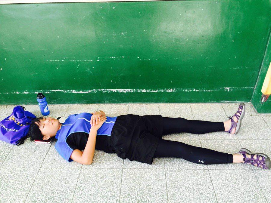 隨行騎車的青年記者李欣恬,累得倒趴在地睡著了。攝影/願景青年記者翁嬿婷
