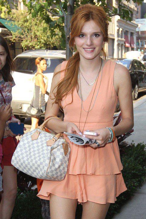 歌手Bella Thorne受邀出席記者會,以一襲粉橘小洋裝搭配Louis Vu...