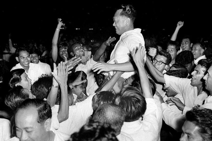 新加坡的選舉式民主與李光耀的「恩賜」;圖維李光耀(中)率領人民行動黨在1963年...