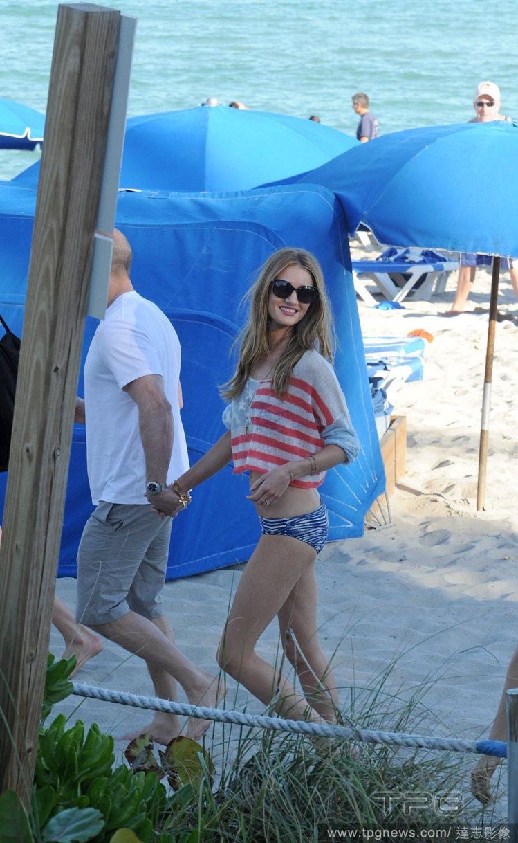 蘿西杭亭頓身穿美國國旗印花短上衣,搭配動物紋泳褲,站在一身灰白的傑森史塔森旁邊,...