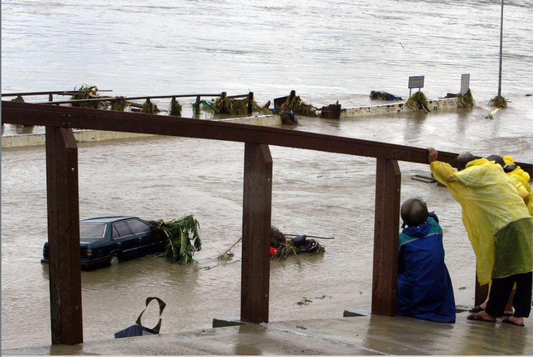 中度颱風艾利讓新北市秀朗橋溪水一度快要淹到橋面,停放在河濱公園和自行車道的車輛全...