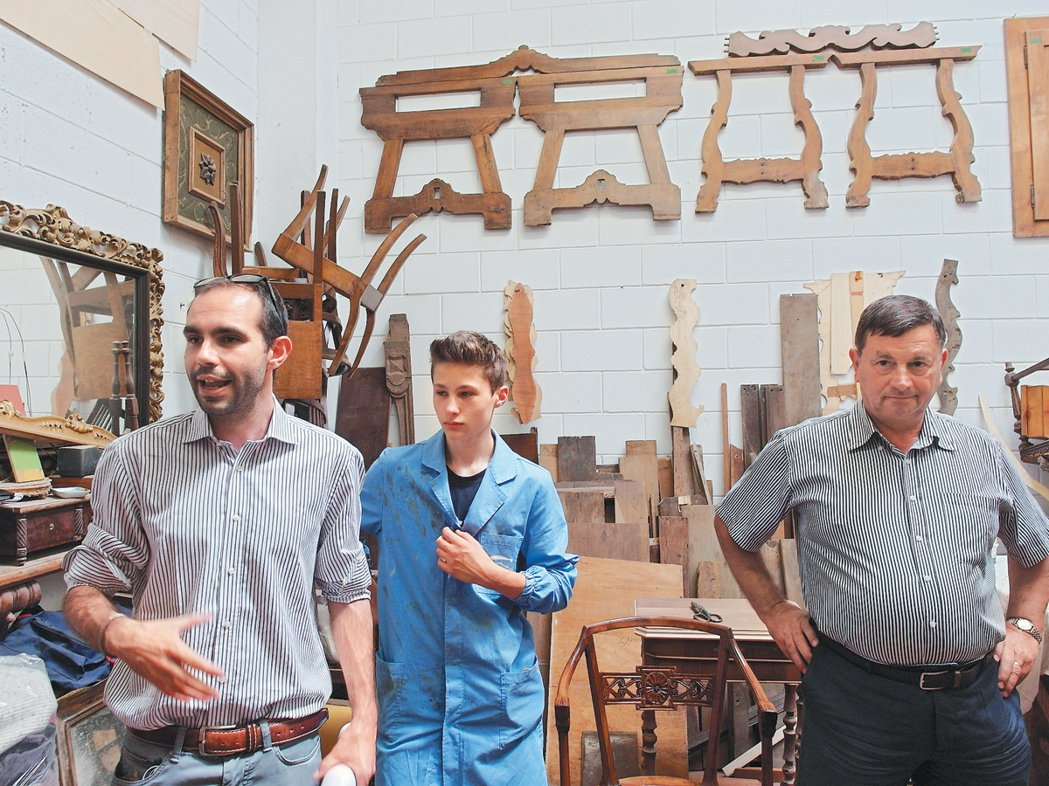 家具工廠內,穿著藍色工作服的學生(中)正認真聽「Cometa」職員納帝(左)向訪...