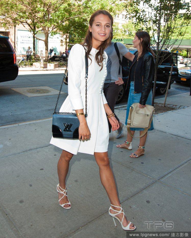 有著花邊點綴的純白洋裝與鏤空高跟鞋,使她化身優雅可愛的淑女。圖/達志影像