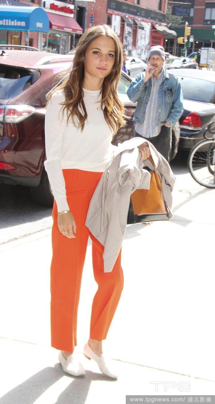 白上衣、橘色褲款與白色樂福鞋的組合,為艾莉西亞維坎德增添悠閒 Tomboy 感受...