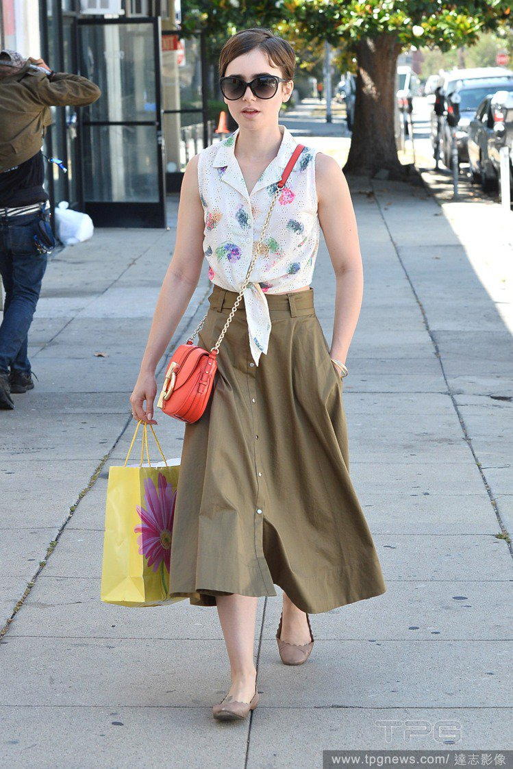 白色削肩襯衫搭配大地色蓬裙原本就相當俏皮,穿一雙平底鞋就有型。紅色包款也點亮了這...
