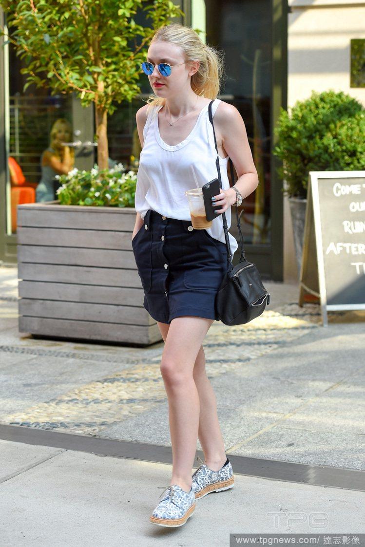 達柯塔芬妮穿了件白背心,搭配鈕扣短裙與休閒鞋,馬尾與彩色墨鏡為她注入俐落氣息。圖...