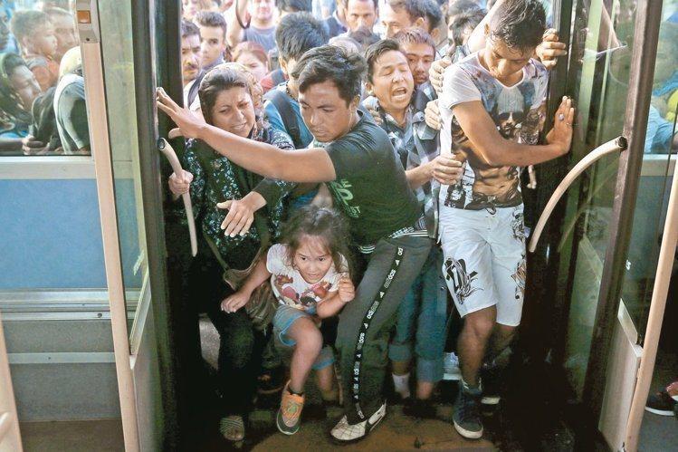 搭乘客輪抵達希臘比雷埃夫斯港的難民,七日爭先恐後搶搭巴士。 路透