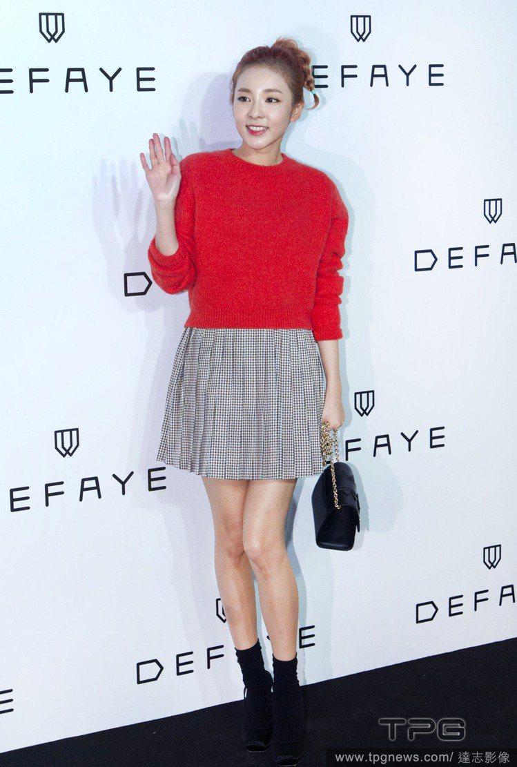 Dara 以紅色針織衫搭配百褶裙、黑襪與黑色高跟鞋,打造初秋甜美學院風。圖/達志...